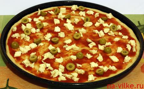 Соус, моцарелла и оливки на пицце