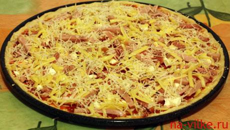 Посыпать пиццу тёртым сыром